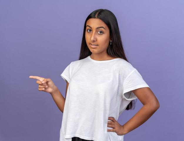 흰색 티셔츠를 입은 어린 소녀가 파란색 배경 위에 서 있는 쪽을 검지 손가락으로 가리키며 자신감 있게 웃고 있는 카메라를 바라보고 있습니다.