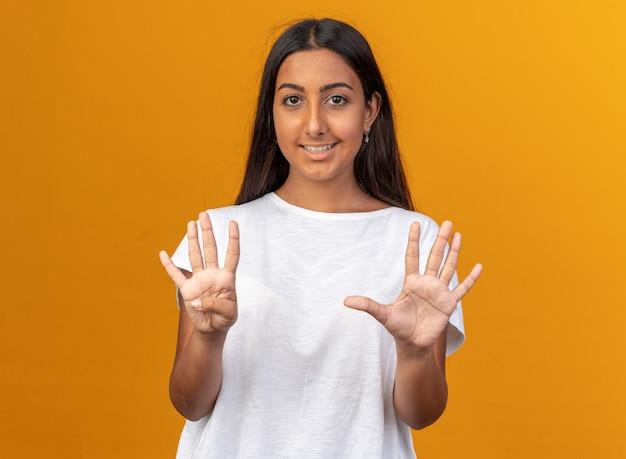Молодая девушка в белой футболке, глядя в камеру, уверенно улыбается, показывая номер восемь