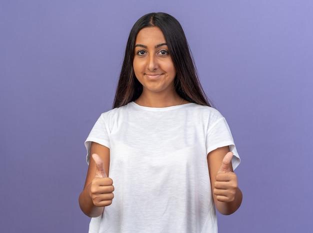 카메라를보고 흰색 티셔츠에 어린 소녀 자신감 보여주는 엄지 손가락 미소