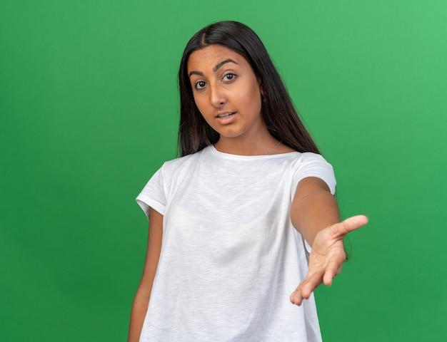 Молодая девушка в белой футболке, глядя в камеру, дружелюбно улыбается и делает жест, стоя на зеленом фоне