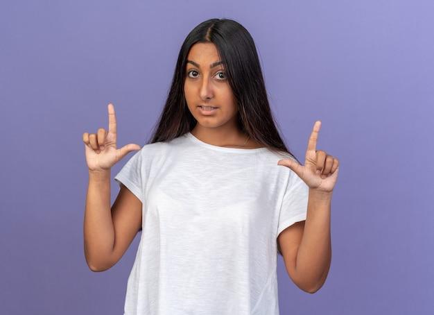카메라를보고 흰색 티셔츠에 어린 소녀 파란색 위에 서있는 검지 손가락을 보여주는 놀란