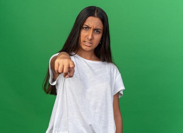 녹색 배경 위에 서 있는 카메라를 검지 손가락으로 가리키는 화난 얼굴로 카메라를 바라보는 흰색 티셔츠를 입은 어린 소녀