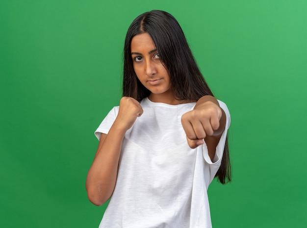 심각한 얼굴로 찾고 권투 선수처럼 포즈 떨리는 주먹으로 카메라를 찾고 흰색 티셔츠에 어린 소녀