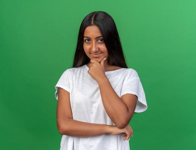 緑の背景の上に立って笑っているあごに手でカメラを見て白いtシャツの少女