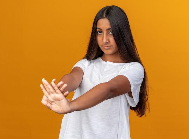 흰색 티셔츠를 입은 어린 소녀가 진지한 얼굴로 카메라를 쳐다보며 주황색 배경 위에 손을 들고 정지 제스처를 취합니다