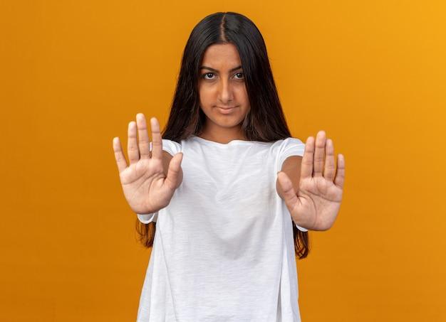 흰색 티셔츠를 입은 어린 소녀가 진지한 얼굴로 카메라를 쳐다보며 주황색 배경 위에 손을 벌린 채 정지 제스처를 취합니다.