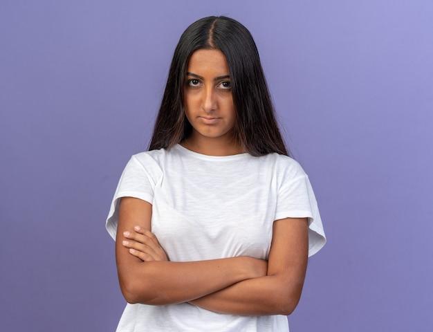 青い背景の上に立って腕を組んで深刻な眉をひそめている顔でカメラを見ている白いtシャツの少女