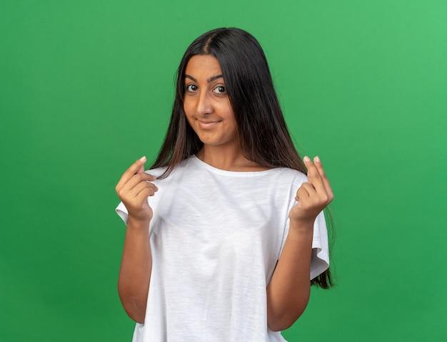 指をこすってお金を稼ぐジェスチャーで笑顔でカメラを見ている白いtシャツの少女