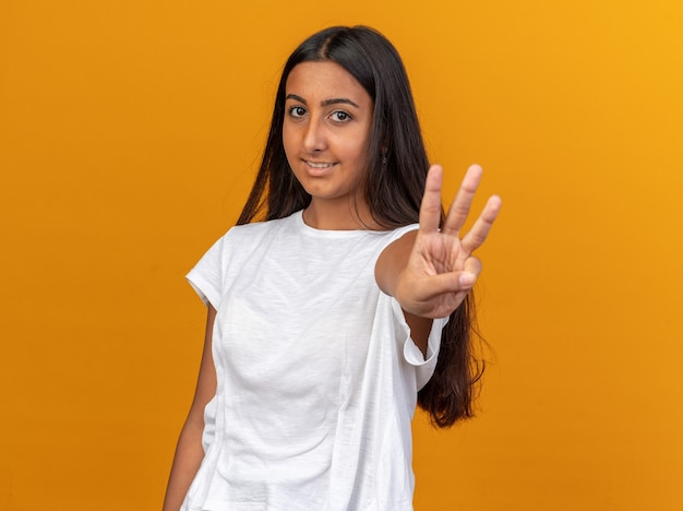 Молодая девушка в белой футболке смотрит в камеру с улыбкой на лице, показывая пальцами номер три