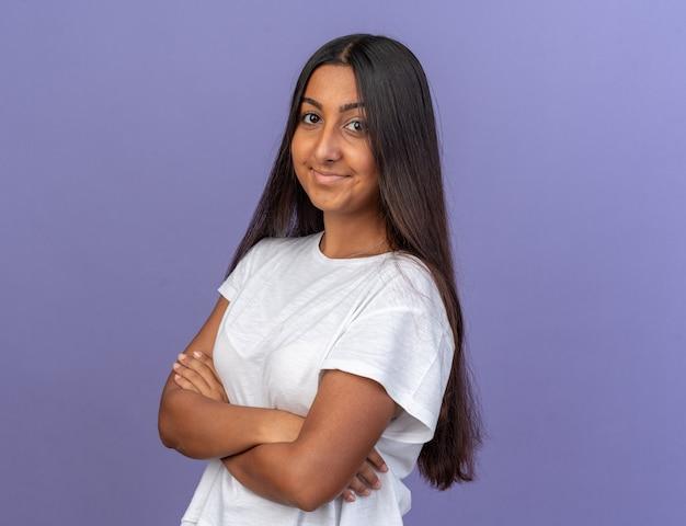 Молодая девушка в белой футболке смотрит в камеру с улыбкой на лице со скрещенными руками, стоя над синим