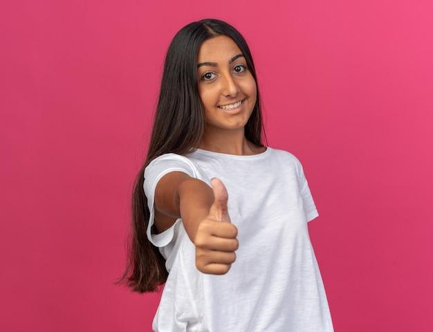 Молодая девушка в белой футболке смотрит в камеру с улыбкой на счастливом лице, показывая пальцы вверх, стоя над розовым