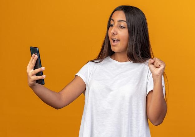 Молодая девушка в белой футболке смотрит на экран своего смартфона, сжимая кулак, счастливая и взволнованная, стоя на оранжевом фоне