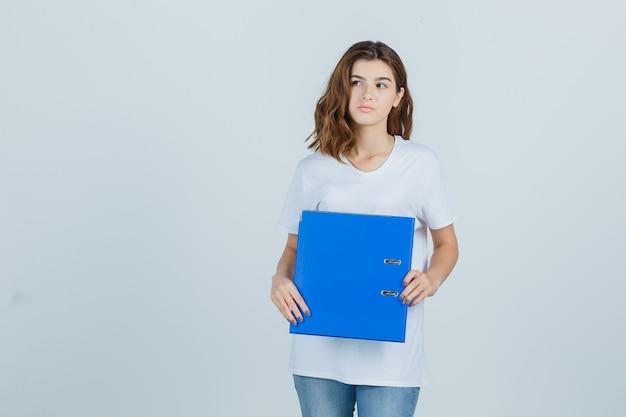 白いtシャツを着た少女がフォルダーを持って目をそらし、焦点を合わせて見ている、正面図。