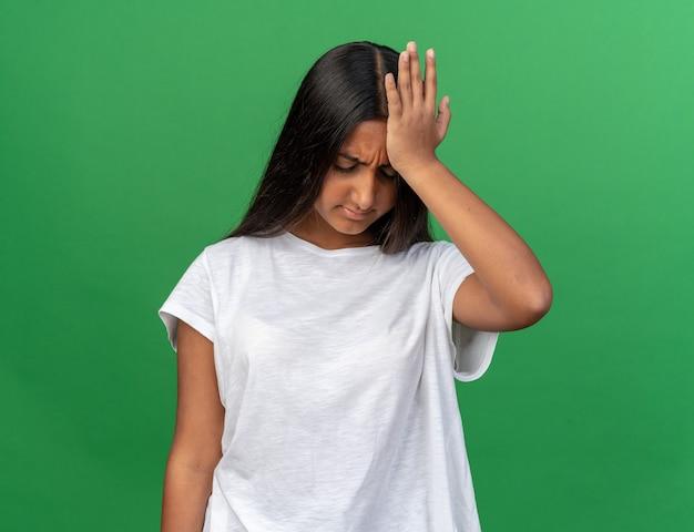 緑の背景の上に立っている彼女の頭の前に手で混乱し、非常に心配そうに見える白いtシャツの少女