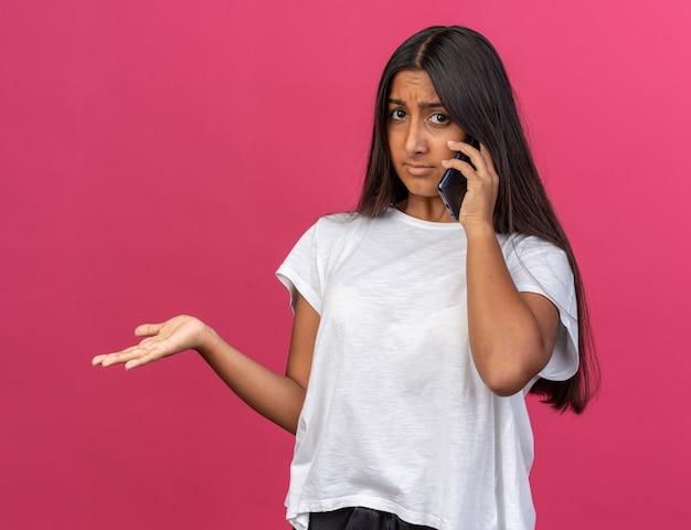 흰색 티셔츠를 입은 어린 소녀가 분홍색 배경 위에 팔을 들고 휴대폰으로 통화하는 동안 혼란스러워 보입니다.