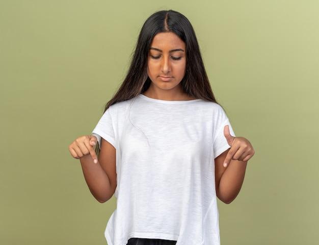 Молодая девушка в белой футболке смотрит вниз с серьезным лицом, указывающим вниз, с указательными пальцами, стоящими над зеленым