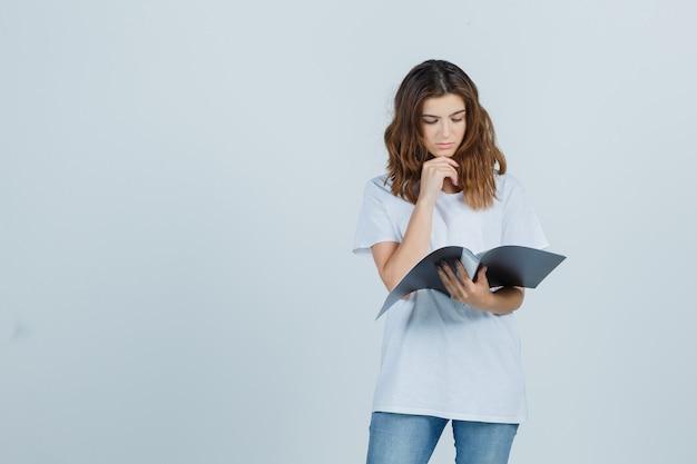 폴더에 메모를보고 주저, 전면보기를 찾고 흰색 티셔츠에 어린 소녀.