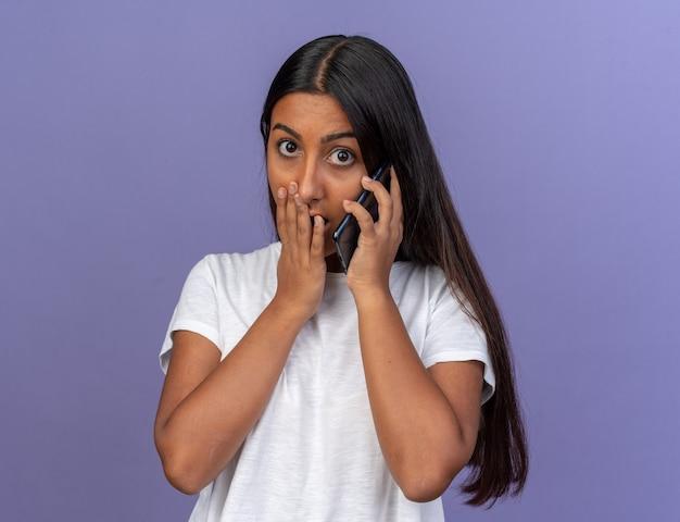 흰색 티셔츠를 입은 어린 소녀가 파란색 배경 위에 서서 휴대폰으로 통화하는 동안 놀란 표정을 짓고 있습니다.
