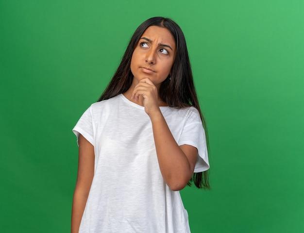 Молодая девушка в белой футболке смотрит вверх озадаченно, положив руку на подбородок, стоя на зеленом фоне
