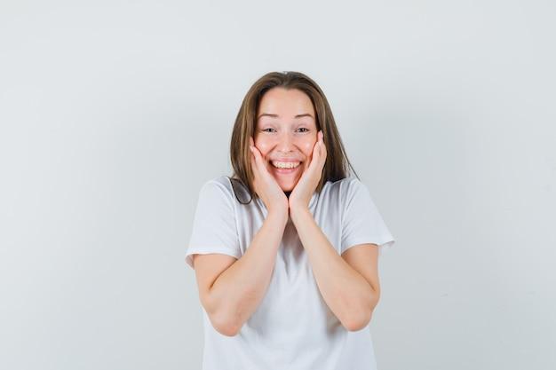 그녀의 손에 얼굴을 베개하고 쾌활한, 전면보기를 찾고 흰색 티셔츠에 어린 소녀.