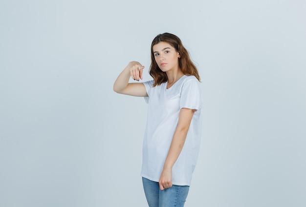 カメラを指して、賢明な正面図を探している白いtシャツの少女。