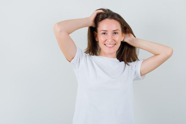 髪の手でポーズをとって、魅力的に見える白いtシャツの少女、正面図。