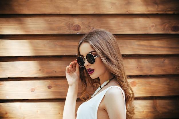 木製の背景にポーズをとって白いtシャツの若い女の子
