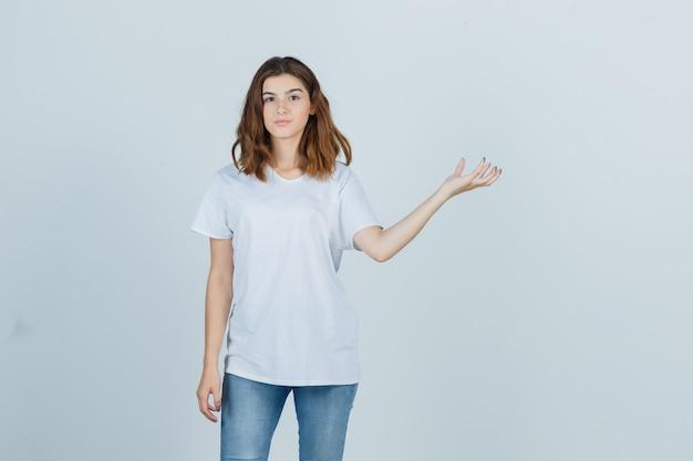 흰색 t- 셔츠에 어린 소녀 뭔가 잡고있는 척 하 고 자신감, 전면보기를 찾고.