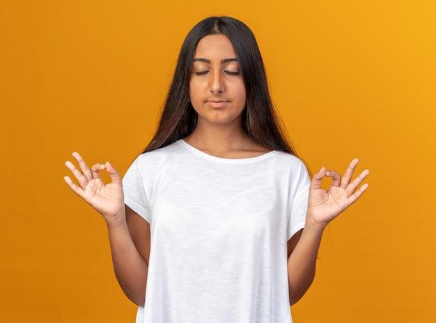 흰색 티셔츠를 입은 어린 소녀가 주황색 배경 위에 서서 눈을 감고 손가락으로 명상 제스처를 하고 있다