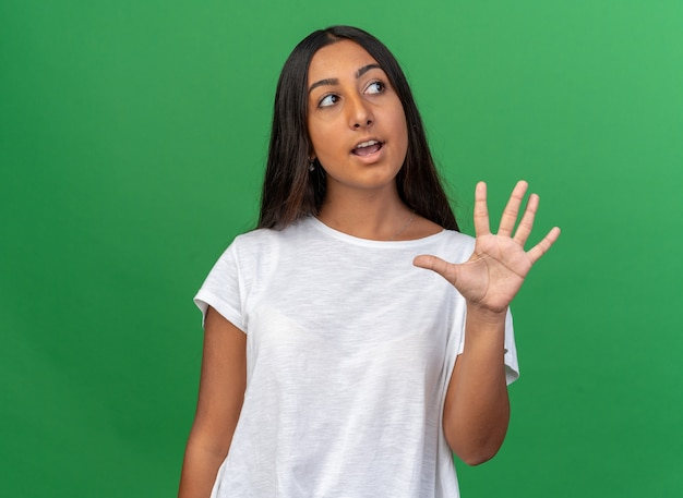 困惑して脇を見て5番を示す白いtシャツの少女
