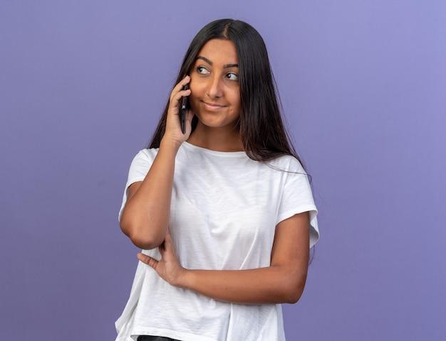 흰색 티셔츠를 입은 어린 소녀가 파란색 배경 위에 서서 휴대폰으로 통화하면서 친절하게 웃고 있습니다.