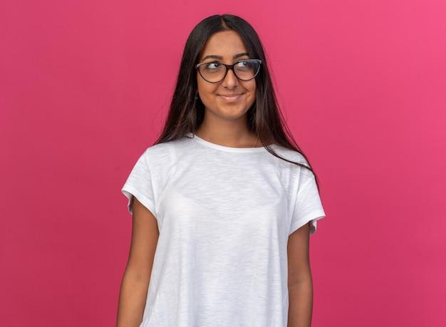 Молодая девушка в белой футболке в очках смотрит в сторону с улыбкой на счастливом лице, стоящем над розовым