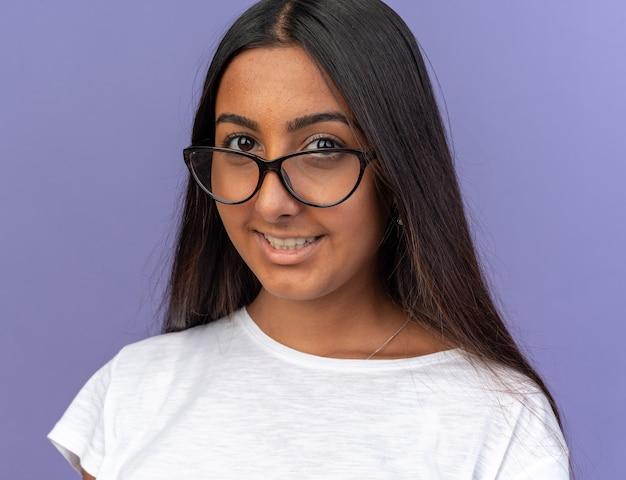 Молодая девушка в белой футболке в очках смотрит в камеру с улыбкой на счастливом лице, стоящем над синим