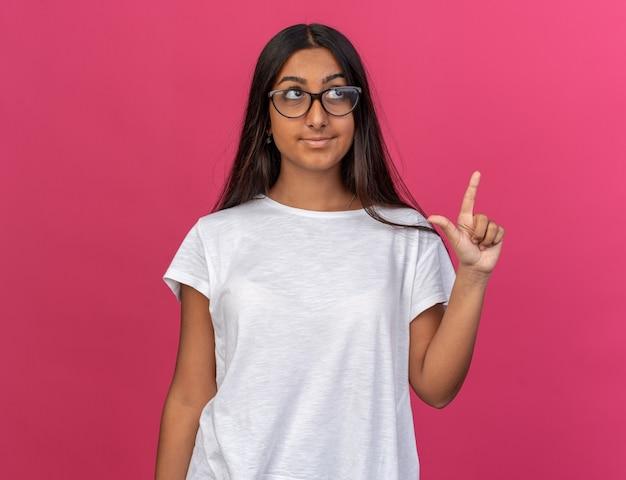 Молодая девушка в белой футболке в очках смотрит вверх с улыбкой на лице, показывая указательный палец, имеющий новую идею, стоящий над розовым