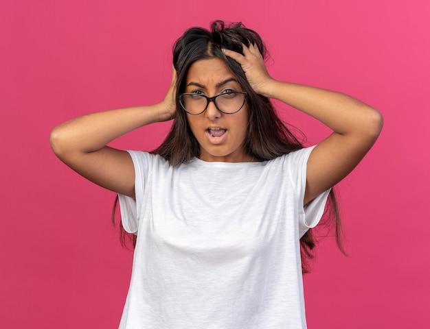 안경을 쓴 흰색 티셔츠를 입은 어린 소녀가 분홍색 배경 위에 서 있는 그녀의 머리를 거칠게 잡아당기고 있다