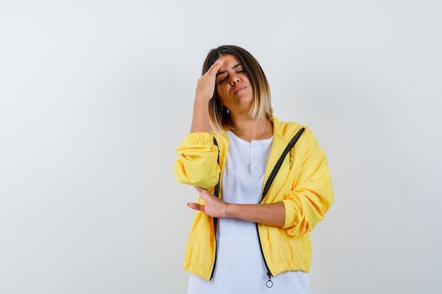 Молодая девушка в белой футболке, желтой куртке, положив руку на лоб, с головной болью и выглядящей измученной, вид спереди.