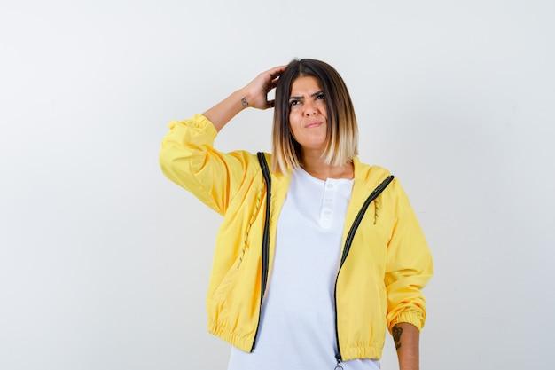 Молодая девушка в белой футболке, желтой куртке почесывает голову, думает о чем-то и смотрит задумчиво, вид спереди.