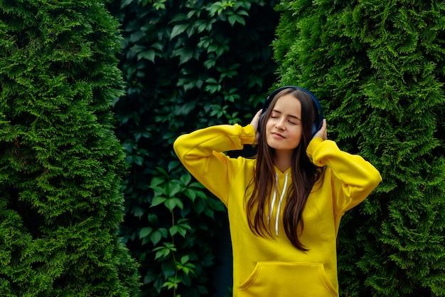 Молодая девушка в беспроводных наушниках на фоне зеленых елок, слушает музыку
