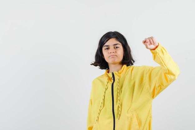 노란색 폭격기 재킷 주먹 떨림과 심각한 찾고 어린 소녀