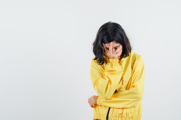 손으로 얼굴을 덮고, 뭔가에 대해 생각하고 잠겨있는 찾고 노란색 폭격기 재킷에 어린 소녀
