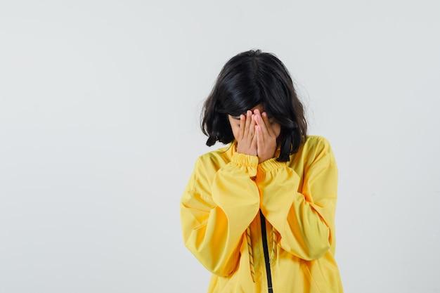 노란색 폭격기 재킷을 입은 어린 소녀가 손으로 입 얼굴을 덮고 유감스럽게 보입니다.