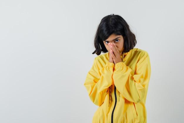 노란색 폭격기 재킷을 입은 어린 소녀가 손으로 입을 덮고 소심 해 보입니다.