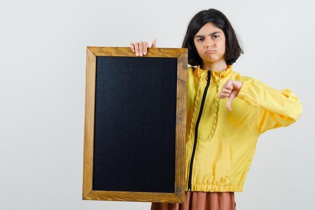 Молодая девушка в желтой куртке-бомбардировщике держит доску, показывает палец вниз и выглядит недовольной