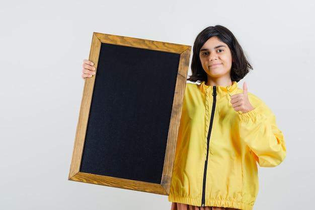 Молодая девушка в желтой куртке-бомбардировщике держит доску, показывает большой палец вверх и выглядит серьезно