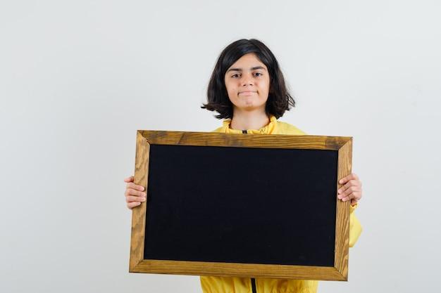 Молодая девушка в желтой куртке-бомбардировщике держит доску обеими руками и выглядит серьезно