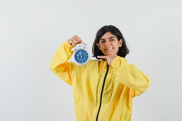 Молодая девушка в желтой куртке-бомбардировщике держит часы, указывая на них указательным пальцем и выглядит счастливой