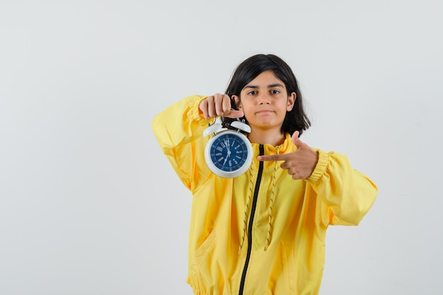 Молодая девушка в желтой куртке-бомбардировщике держит часы, указывая на них указательным пальцем и серьезно выглядит