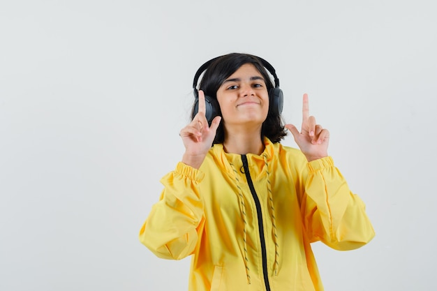 Молодая девушка в желтой куртке-бомбардировщике слушает музыку в наушниках, указывая указательными пальцами вверх и выглядит счастливой