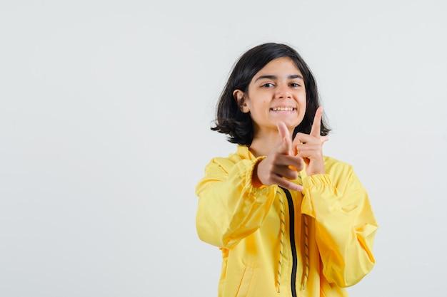 검지 손가락으로 카메라를 가리키고 행복을 찾고 노란색 폭격기 재킷에 어린 소녀