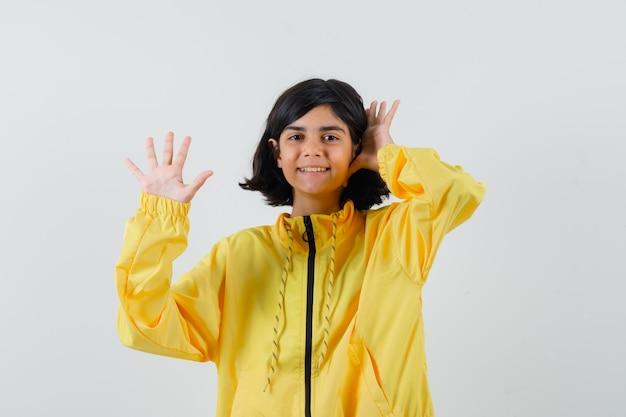 Молодая девушка в желтой куртке-бомбардировщике поднимает руки, приветствуя кого-то и выглядит счастливой